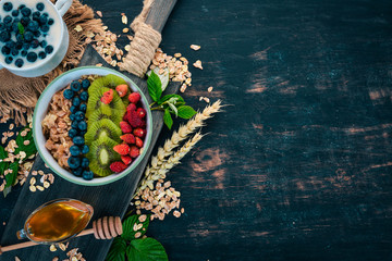 Oatmeal with blueberry strawberries and kiwi. On a wooden background. Top view. Free space for text.