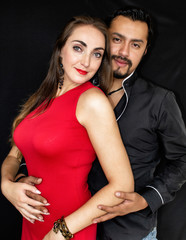 Love story, man and woman brunettes hugging on a black background.Love story, man and woman brunettes hugging on a black background.