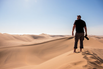 Vibrant Image of a photographer stood on Dune 7 with the surrounding sand dunes near Swakopmund, Namibia, Africa, in the background