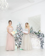 Happy women holding gifts over by the Christmas tree