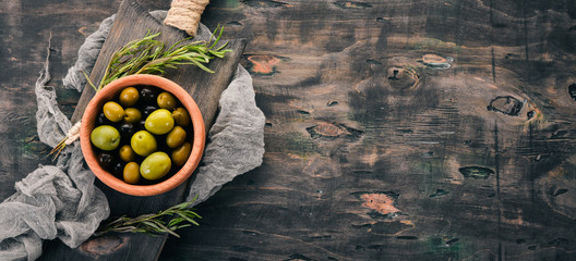 Olives in a plate and rosemary. On a black wooden background. Free space for text. Wall mural