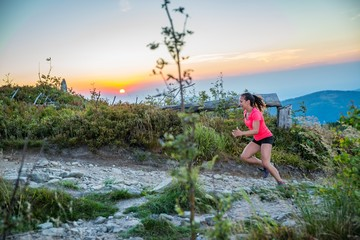 Woman trail running in mountains.