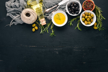 A set of olives and olive oil and rosemary. Green olives and black olives. On a black wooden background. Free space for text.