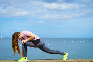 Woman stretching legs next to sea