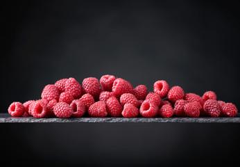 Ripe raspberries on a black background.