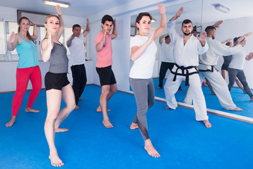 adults attempting to master new moves during karate class