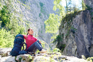 Smiling female tourist resting on rock admiring beauty of breathtaking rocky mountains in spectacular place in Romania. Woman climber positive happy travel healthy life sunny day grassy hill view