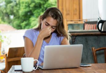 Blonde Frau mit Schlafmangel hat Kopfschmerzen