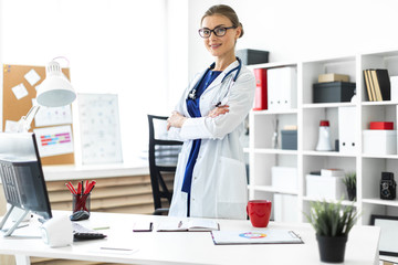 A young girl in a white coat is standing near a table in her office. A stethoscope hangs around her neck.