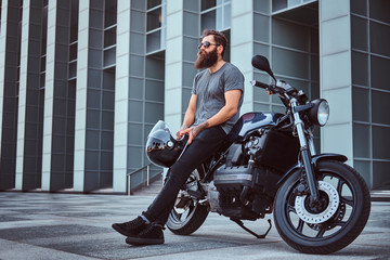 Brutal bearded male in a gray t-shirt and black pants holds a helmet sitting on his custom-made retro motorcycle against skyscraper. Wall mural
