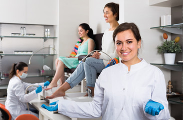 Smiling woman nail technician welcoming to modern beauty salon