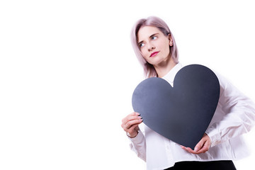 Young beautiful blonde woman in a white shirt holding black chalkboard on white background. Greeting for valentine's day. Close-up portrait