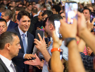 Canada's Prime Minister Justin Trudeau greets employees as he arrives for a press conference at CAE Inc., in Montreal, Quebec