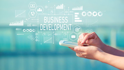 Business Development with person holding a white smartphone