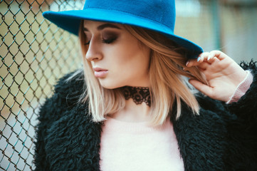 Close up portrait of attractive young hipster woman in black fur coat and blue hat standing near the old fance in the autumn park.