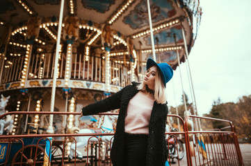 Beautiful stylish blonde woman in black fur coat and blue hat posing near the carousel in theme park.