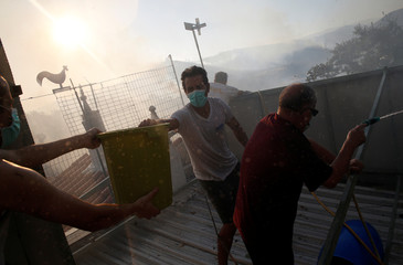 People on a rooftop help to put out a fire in Enxerim, Silves