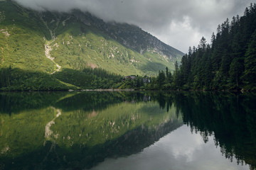 Foggy green mountain forrest and hills with a reflection on the lake, morskie Oko in High Tatras, Zakopane, Poland