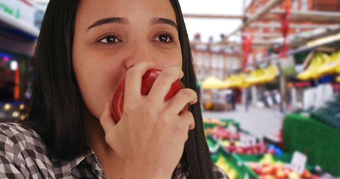 Hispanic girl munches on crisp red apple bought from outdoor fruit vendor