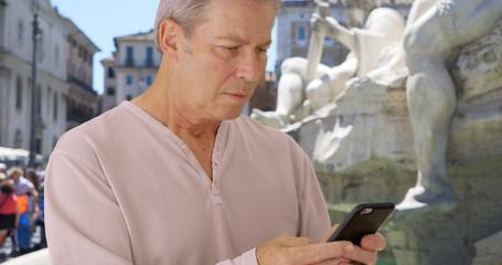 Old Caucasian male in Rome uses smartphone near Fontana dei Quattro Fiumi