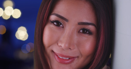 Portrait of gorgeous Asian female smiling at camera outdoors at night
