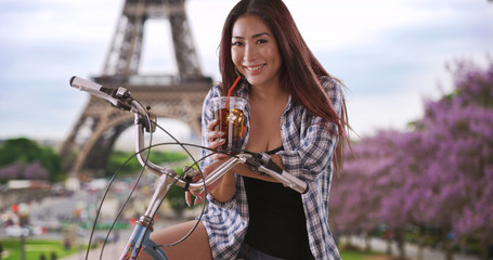 Cute Japanese woman smiling and drinking her tea near Eiffel Tower