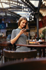 Woman In Cafe Taking Food Photo On Mobile Phone