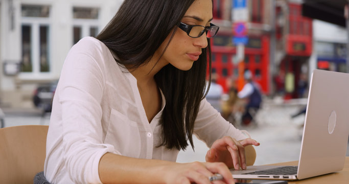 Latina businesswoman with glasses sits at table outdoors using laptop