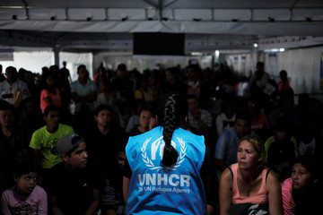 A member of United Nations High Commissioner for Refugees talks with Venezuelans as they queue in line to receive a vaccine after showing their passports or identity cards at the Pacaraima border control