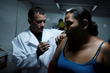 Venezuelan woman receives a free vaccination given by a volunteer after showing her passport at the Pacaraima border control