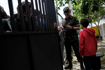 A military officer looks at a passport of a Venezuelan woman as people queue in line at the Pacaraima border control