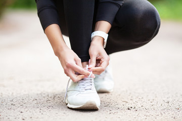Fitness. Woman Runner Tightening Shoe Lace. Runner Woman Feet Running On Road Closeup On Shoe