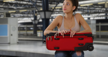 Pensive young Latin woman waits with suitcase at subway station