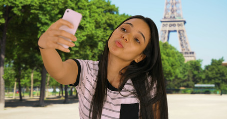 Latina female near Eiffel Tower taking selfies to post on social media