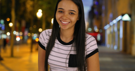 Portrait of happy attractive Latin female on Champs Elysees avenue at night