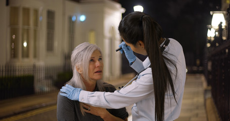 Latina woman doctor checks mature womans eyes on street at night