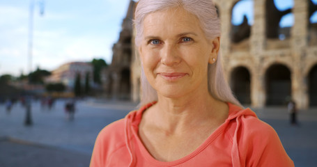 Smiling portrait of cute mature woman near Colosseum in Rome Italy