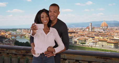 Attractive couple take selfies with Florence cityscape to share on social media