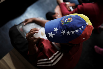 A Venezuelan woman wears a cap with the colours of Venezuelan flag as she drinks coffee with milk after receiving a free vaccination and showing her passport at the Pacaraima border control