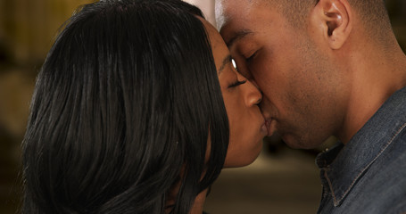 African-American girlfriend and boyfriend kiss with passion on night out