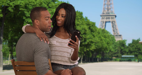 Loving African-American couple have nice chat while sitting near Eiffel Tower