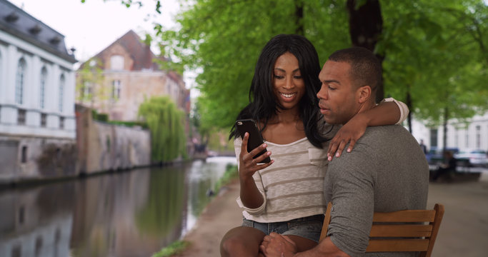 Attractive ethnic female sitting on boyfriends lap looking at smart phone