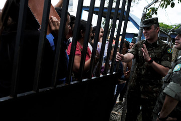 A military officer talks to Venezuelans as they queue to show their passports or identity cards at the Pacaraima border control