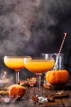 Autumn pumpkin cocktail on wooden table.