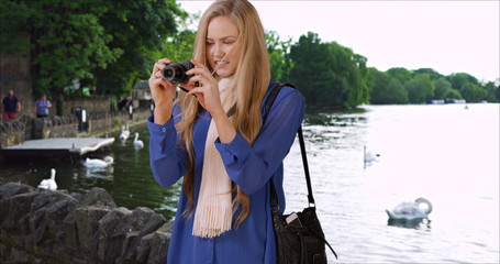 White female tourist taking photos while on vacation in Windsor England