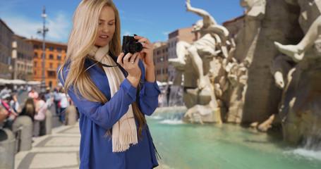 Caucasian tourist vacationing in Rome taking photos near Fiumi Fountain