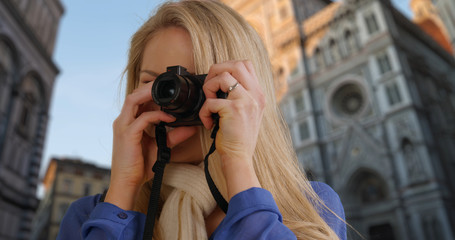 Happy white female traveling in Florence takes photos near Florence Cathedral
