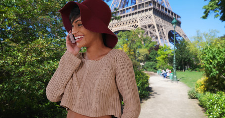 Young African-American female near Eiffel Tower calls home on cellphone