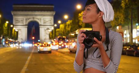 Female African photographer taking photos in Paris outside near Arc de Triomphe