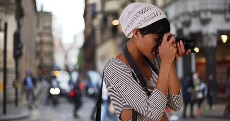 Modern black woman millennial taking shots of London city on camera